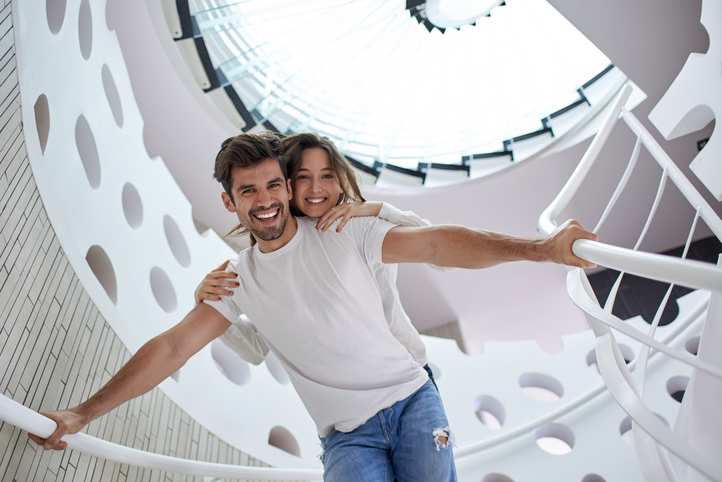 relaxed young couple on spiral glass stairs in modern home villa indoors